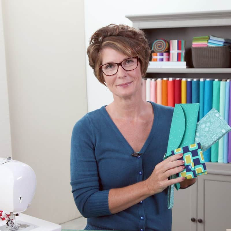 Deby holding several wallets sewn in the Craftsy Sewing Wallets class